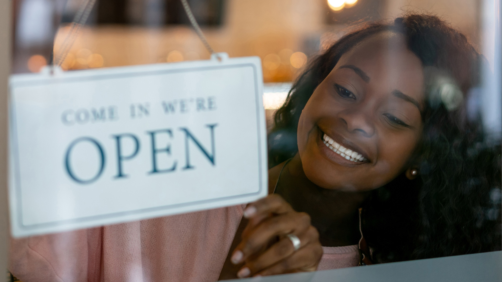 "A young woman places ""come in we're open"" sign in her business window"