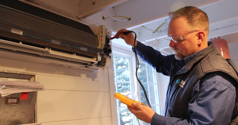 Technician from Rolls Mechanical works on an air conditioner