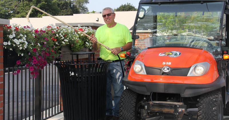 Swartz Creek employee watering city flowers